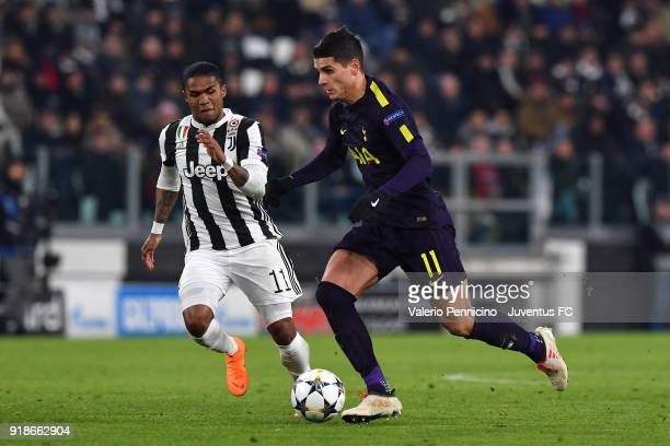 Douglas Costa of Juventus competes with Erik Lamela of Tottenham Hotspur during the UEFA Champions League Round of 16 First Leg match between...