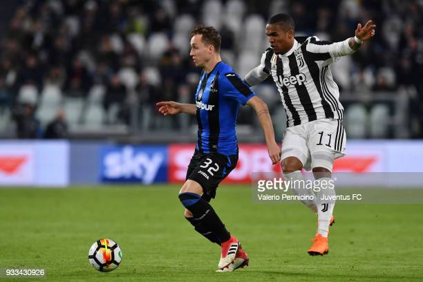Douglas Costa of Juventus competes with Nicolas Haas of Atalanta BC during the Serie A match between Juventus and Atalanta BC on March 14 2018 in...
