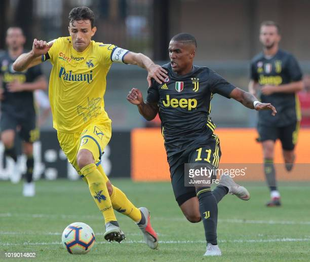 Douglas Costa of Juventus FC competes for the ball with Ivan Radovanovic of Chievo Verona during the serie A match between Chievo Verona and Juventus...