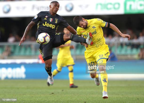 Douglas Costa of Juventus FC competes for the ball with Nenad Tomovic of Chievo Verona during the Serie A match between Chievo Verona and Juventus at...