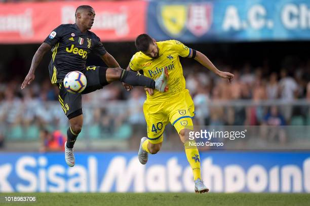 Douglas Costa of Juventus FC competes for the ball with Nenad Tomovic of AC ChievoVerona during the Serie A football match between AC ChievoVerona...