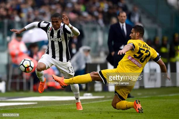 Douglas Costa of Juventus FC is tackled by Ali Adnan of Udinese Calcio during the Serie A football match between Juventus FC and Udinese Calcio...