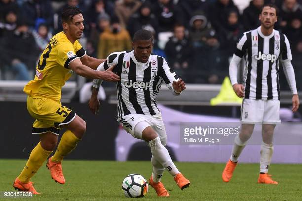 Douglas Costa of Juventus in action Ali Adnan of Udinese tackles during the serie A match between Juventus and Udinese Calcio on March 11 2018 in...