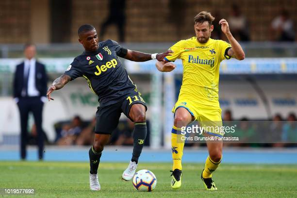 Douglas Costa of Juventus in action with Nicola Rigoni of Chievo Verona during the Serie A match between Chievo Verona and Juventus at Stadio...