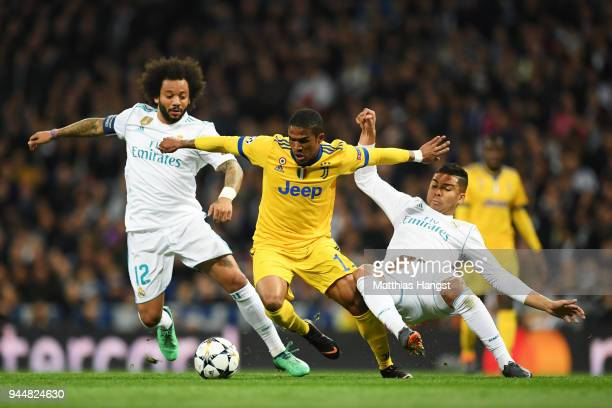 Douglas Costa of Juventus is challenged by Marcelo of Real Madrid and Casemiro of Real Madrid during the UEFA Champions League Quarter Final Second...