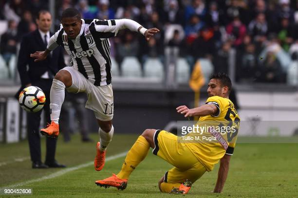 Douglas Costa of Juventus jumps as Ali Adnan of Udinese tackles during the serie A match between Juventus and Udinese Calcio on March 11 2018 in...