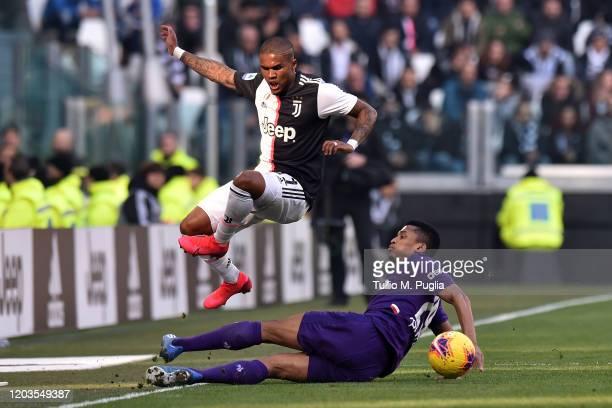 Douglas Costa of Juventus jumps as Dalbert of Fiorentina tackles during the Serie A match between Juventus and ACF Fiorentina at Allianz Stadium on...