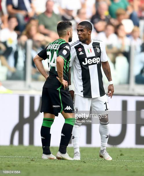 Douglas Costa of Juventus spits to Federico Di Francesco of Sassuolo during the serie A match between Juventus and US Sassuolo at Allianz Stadium on...