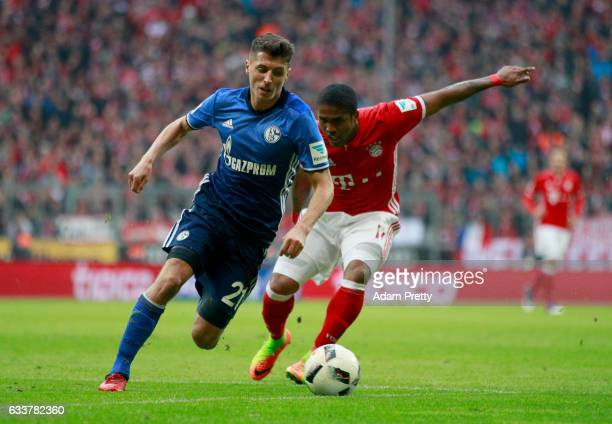 Douglas Costa of Muenchen and Alessandro Schoepf of Schalke jump to head for the ball during the Bundesliga match between Bayern Muenchen and FC...