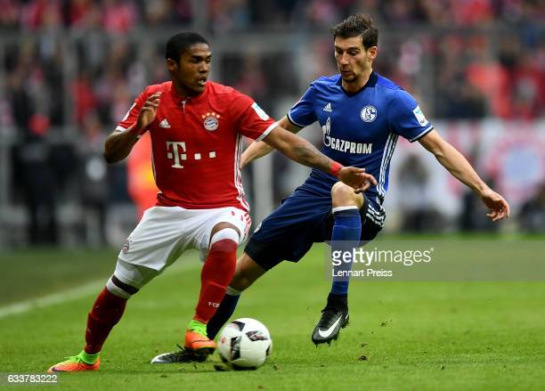 Douglas Costa of Muenchen and Leon Goretzka of Schalke battle for the ball during the Bundesliga match between Bayern Muenchen and FC Schalke 04 at...