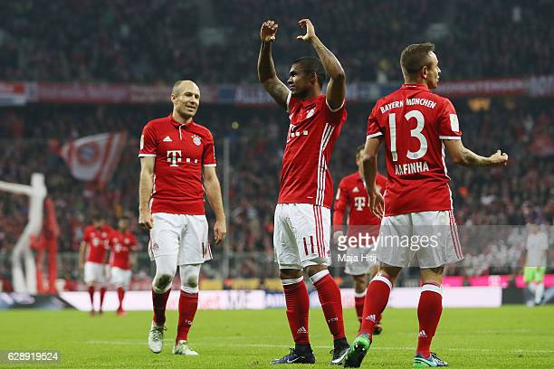 Douglas Costa of Muenchen celebrates his team's fifth goal with team mates Rafinha and Arjen Robben during the Bundesliga match between Bayern...