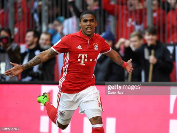 Douglas Costa of Muenchen celebrates scoring his side's second goal during the Bundesliga match between Bayern Muenchen and Eintracht Frankfurt at...