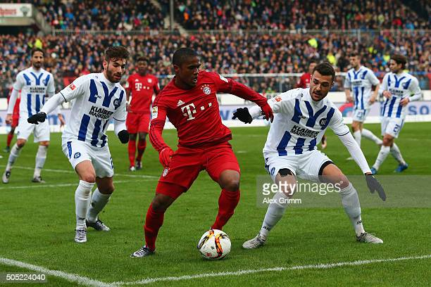 Douglas Costa of Muenchen is challenged by Enrico Valentini and Manuel Gulde of Karlsruhe during a friendly match between Karlsruher SC and FC Bayern...