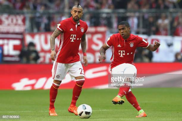 Douglas Costa of Muenchen runs with the ball with his team mate Arturo Vidal during the Bundesliga match between Bayern Muenchen and Eintracht...