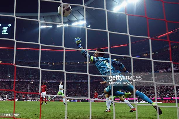 Douglas Costa of Muenchen scores his team's fifth goal past goalkeeper Diego Benaglio of Wolfsburg during the Bundesliga match between Bayern...