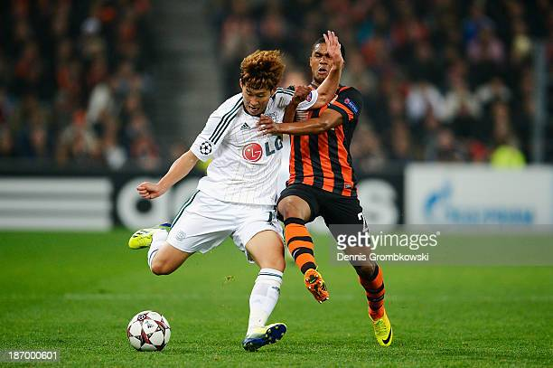 Douglas Costa of Shakhtar Donetsk challenges HeungMin Son of Bayer Leverkusen during the UEFA Champions League Group A match between Shakhtar Donetsk...