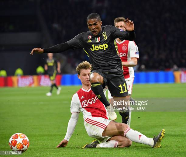 Douglas Costaof Juventus is challenged by Frenkie De Jong of Ajax during the UEFA Champions League Quarter Final first leg match between Ajax and...