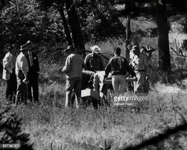 Douglas County officers and FBI men shown clustering around spot in the wooded hills southwest of Sedalia Colo where the bones of Adolph Coors III...