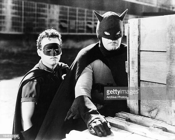 Douglas Croft and Lewis Wilson hide behind crates in a scene from the film 'Batman', 1943.