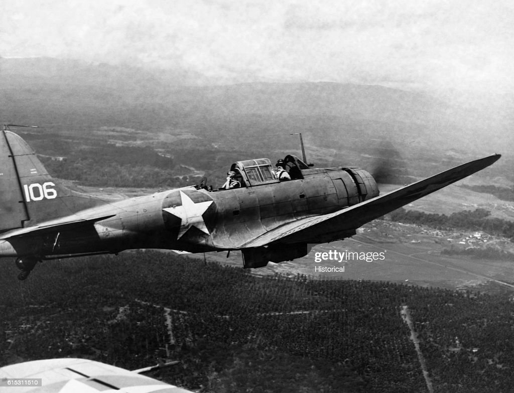 A Douglas Dauntless dive bomber flies over fields while on a