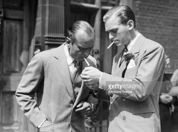 Douglas FAIRBANKS junior gives Douglas senior a light during a stroll in London around 1935