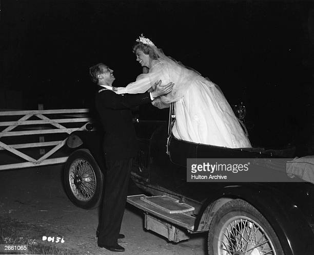 Douglas Fairbanks Junior lifts his new bride, played by Yolande Donlan, out of the wedding car in the film 'Mr Drake's Duck', and directed by Val...