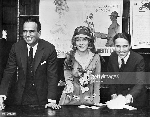 Douglas Fairbanks, Sr., Mary Pickford, and Charlie Chaplin at a World War I Victory Bond Rally. Pickford wears a suit designed by Lady Duff-Gordon...