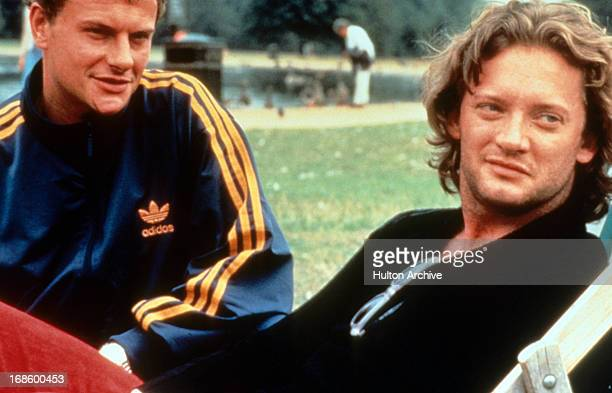 Douglas Henshall sitting at a park in a scene from the film 'If Only' 1998