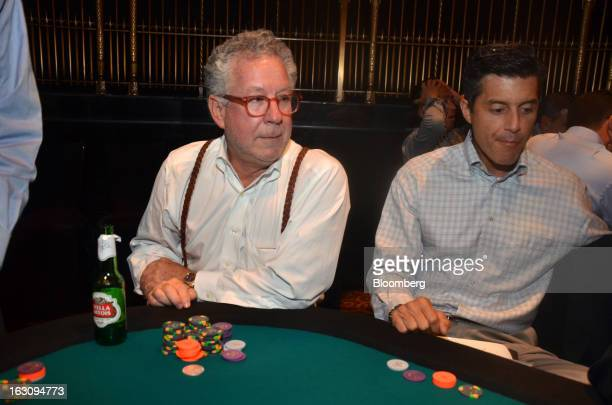 Douglas Kass, president of Seabreeze Partners Management Inc.,left, plays a card game the Reach poker tournament at Gotham Hall in New York, U.S., on...