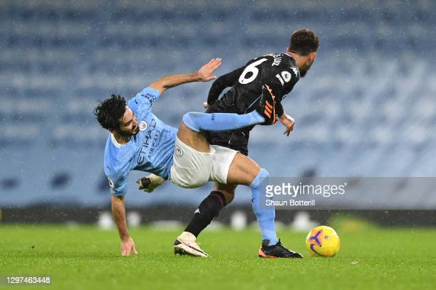 Douglas Luiz of Aston Villa battles for possession with İlkay Gundogan of Manchester City during the Premier League match between Manchester City and...