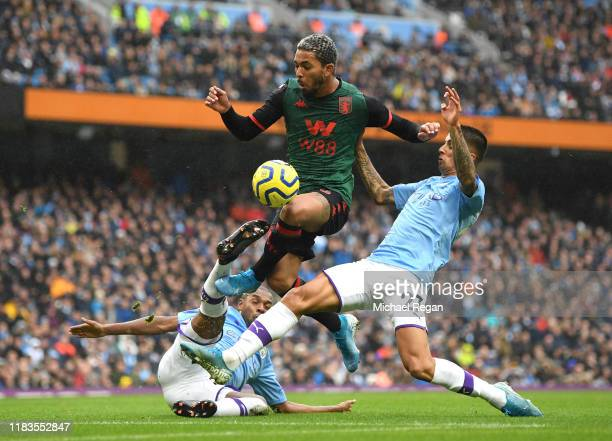 Douglas Luiz of Aston Villa is challenged inside the penalty area by Joao Cancelo and Fernandinho of Manchester City during the Premier League match...