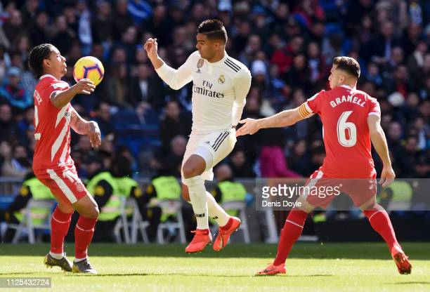 Douglas Luiz of Girona challenges for the ball with Casemiro of Real Madrid during the La Liga match between Real Madrid CF and Girona FC at Estadio...