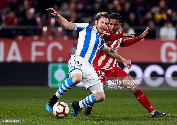 Douglas Luiz of Girona FC competes for the ball with David Zurutuza of Real Sociedad during the La Liga match between Girona FC and Real Sociedad at...
