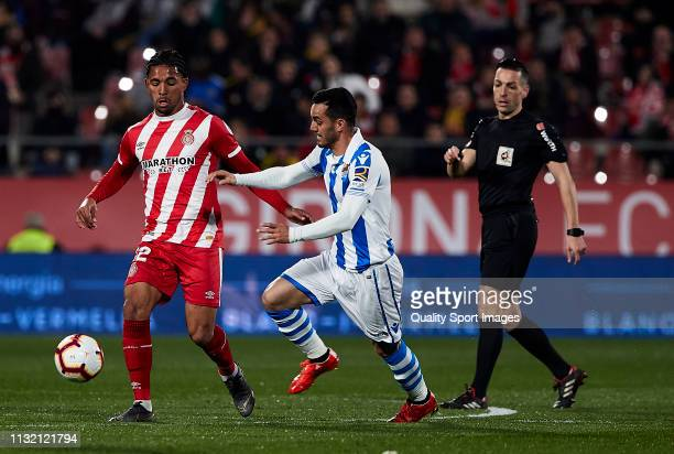 Douglas Luiz of Girona FC competes for the ball with Juanmi Jimenez of Real Sociedad during the La Liga match between Girona FC and Real Sociedad at...