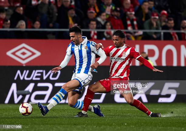 Douglas Luiz of Girona FC competes for the ball with Mikel Merino of Real Sociedad during the La Liga match between Girona FC and Real Sociedad at...