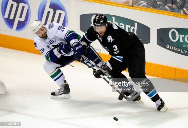 Douglas Murray of the San Jose Sharks and Christopher Higgins of the Vancouver Canucks vie for position to the puck in the second period in Game Four...