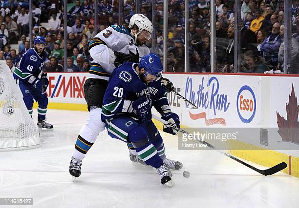 Douglas Murray of the San Jose Sharks and Christopher Higgins of the Vancouver Canucks vie for puck possession in the corner in the second period in...