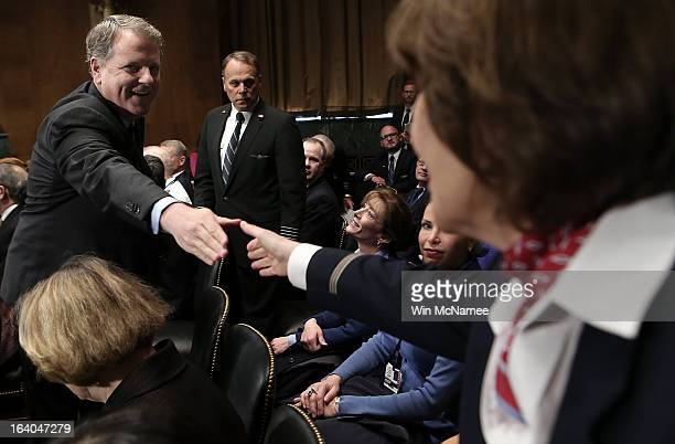Douglas Parker chairman and CEO of the US Airways Group greets flight attendants and other airline employees before a hearing of the Senate Judiciary...