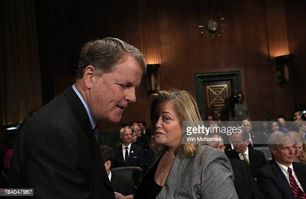 Douglas Parker chairman and CEO of the US Airways Group speaks with lobbyist Hillary Rosen before a hearing of the Senate Judiciary Committee on...