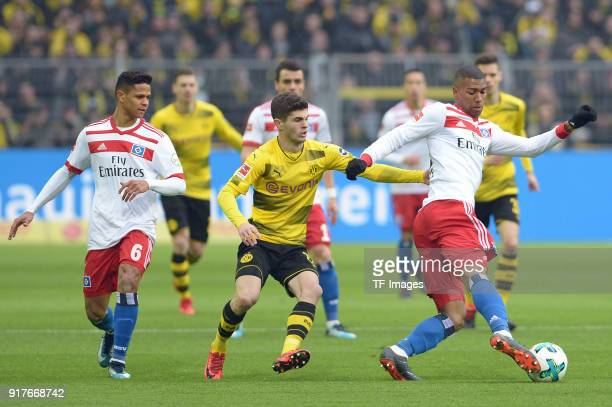 Douglas Santos of Hamburg and Christian Mate Pulisic of Dortmund and Walace of Hamburg battle for the ball during the Bundesliga match between...