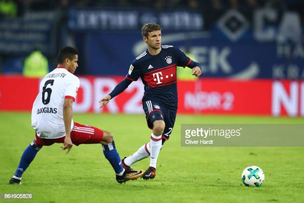 Douglas Santos of Hamburg and Thomas Mueller of Muenchen compete for the ball during the Bundesliga match between Hamburger SV and FC Bayern Muenchen...