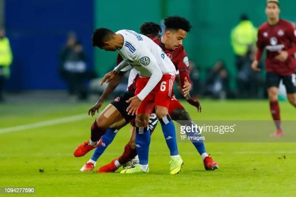 Douglas Santos of Hamburger SV Bakery Jatta of Hamburger SV and Matheus Pereira of 1 FC Nuernberg battle for the ball during the DFB Cup match...
