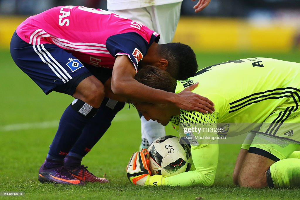 Douglas Santos (L) of Hamburger SV congratulates team mate and Goalkeeper, Rene Adler after he makes a save in the final minutes during the Bundesliga match between Borussia Moenchengladbach and Hamburger SV at Borussia-Park on October 15, 2016 in Moenchengladbach, Germany.