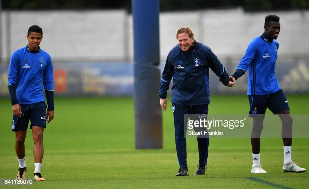 Douglas walks on as Head Coach Markus Gisdol grips Bakery Jatta during a training session of Hamburger SV on August 31, 2017 in Hamburg, Germany.