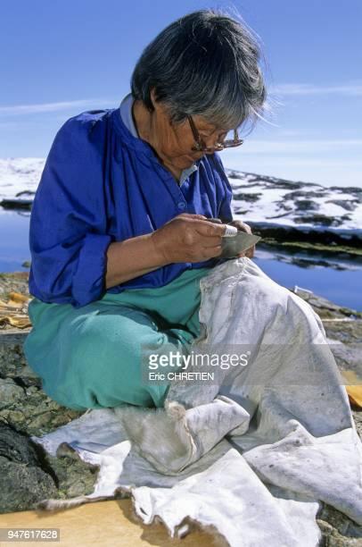 Doumidia utilise son oulou pour couper le fil de la couture qu'elle vient de terminer sur l'emplacement d'une patte A son doigt un de a coudre...