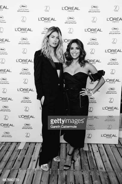 Doutzen Kroes and Eva Longoria pose for photographs at the L'Oreal paris beach on May 23, 2017 in Cannes, France.