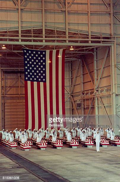 With a huge American flag as a backdrop members of the honor guard stand at attention at the foot of each of the 36 flag drapped coffins during...