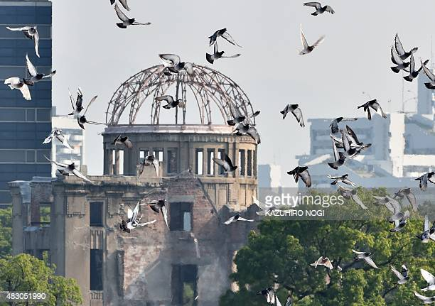 Doves fly over the Hiroshima Peace Memorial Park in western Japan on August 6 2015 during a memorial ceremony to mark the 70th anniversary of the...