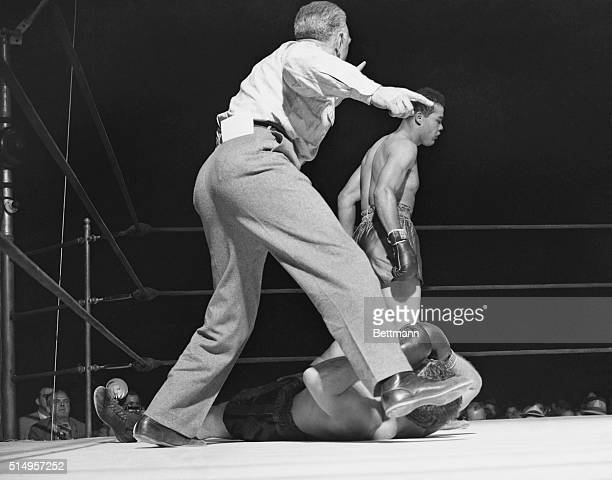Down and Out. New York: Eddie Josephs, the third man in the ring, gestures to Joe Louis to get himself into a neutral corner before starting to count...