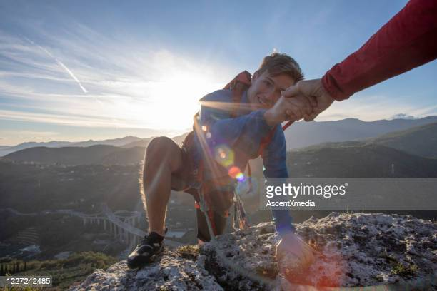 pov down arm to young man climbing up a rock face - reaching stock pictures, royalty-free photos & images